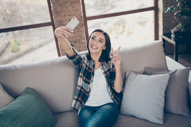 Zdjęcie uroczej pani trzymającej telefon robiącej selfie na blogu z symbolem v siedzącej wygodnej sofie w swobodnej koszuli w kratę i dżinsach w pomieszczeniu