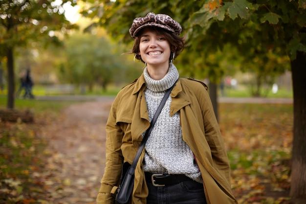 Zdjęcie uroczej pozytywnej młodej, krótkowłosej kobiety o swobodnej fryzurze, wyglądającej wesoło z szerokim uśmiechem podczas spaceru alejką parkową wśród pożółkłych drzew