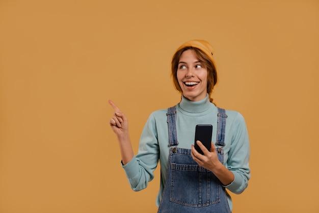 Zdjęcie uroczej rolniczki trzyma punkty smartfona po lewej stronie obrazu. nosi dżinsowy kombinezon i kapelusz, na białym tle brązowy kolor tła.