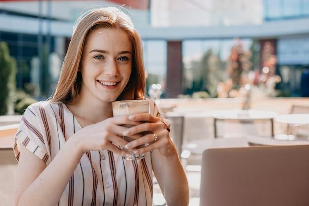 Zdjęcie uroczej rudowłosej dziewczyny pijącej koktajl i cieszącej się przerwą przed rozpoczęciem pracy przy komputerze