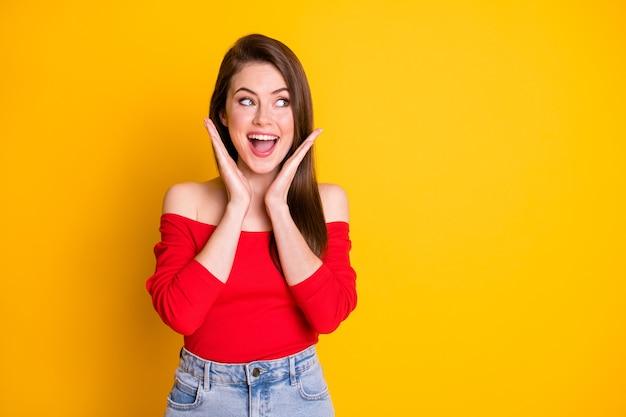 Zdjęcie uroczej ślicznej szalonej młodej dziewczyny zdziwionej otwartymi ustami podniesionymi rękami twarz dłonie rabat ulubione buty linia nosić koszula otwarte ramiona na białym tle żywy żółty kolor tła