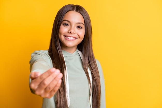 Zdjęcie uroczej, uroczej dziewczynki ubranej na co dzień w zielony strój, zapraszającej do przyjścia na białym tle w kolorze żółtym