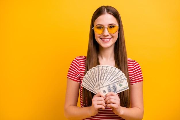 Zdjęcie uroczej uroczej młodej dziewczyny trzymaj pieniądze dolary wentylator weź kredyt marzy spędzać wakacje egzotyczny kraj nosić okulary przeciwsłoneczne w paski biała czerwona koszula wibrujący żółty kolor tła