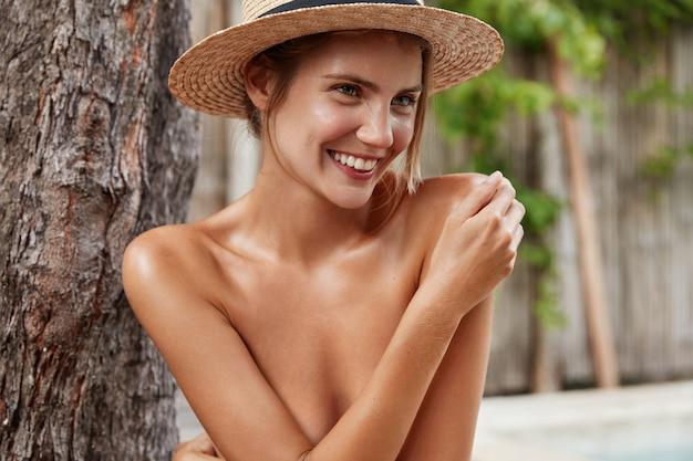Zdjęcie uroczej, uroczej, młodej modelki ma nagie idealne ciało, chowa się ręką, nosi słomkowy kapelusz, ma przyjemny uśmiech, demonstruje doskonałą, zdrową skórę,