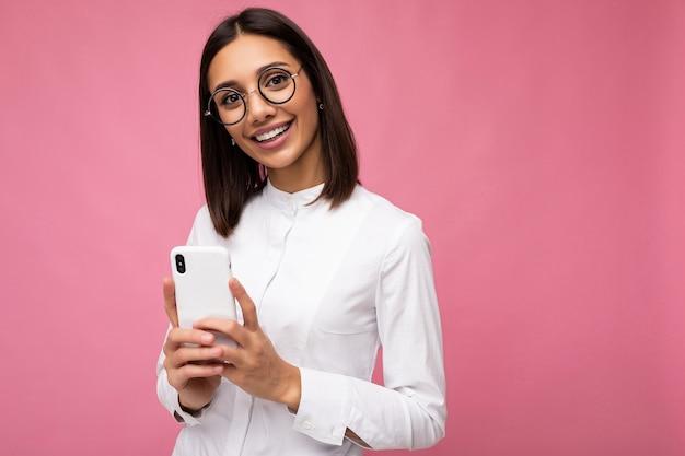 Zdjęcie uroczej uśmiechniętej młodej kobiety brunetka ubrana w białą bluzkę i okulary optyczne stojąc na białym tle nad różowym tle wiadomości sms przy użyciu telefonu komórkowego patrząc na kamery. skopiuj miejsce
