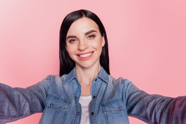 Zdjęcie uroczej zadowolonej kobiety sprawia, że selfie promienny uśmiech wygląda na aparat na tle różowego koloru