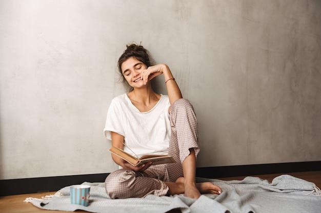 Zdjęcie uroczej zdumionej kobiety noszącej ubrania rekreacyjne, pijącej kawę i czytającej książkę, siedząc na podłodze w domu