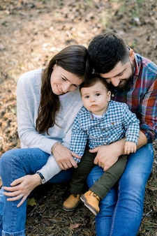 Zdjęcie uroczych rodziców przytulających małego synka, w jesiennym parku lub lesie, siedzących razem i spędzających czas z rodziną, bawiąc się na świeżym powietrzu