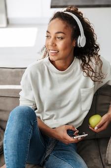 Zdjęcie uśmiechnięta african american kobieta noszenie słuchawek za pomocą telefonu komórkowego, siedząc na kanapie w jasnym mieszkaniu
