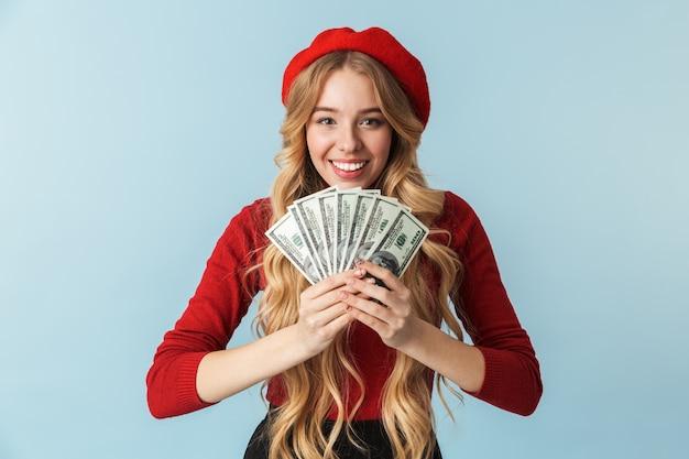 Zdjęcie uśmiechnięta blond kobieta 20s ubrana w czerwony beret, trzymając kilka banknotów pieniędzy na białym tle