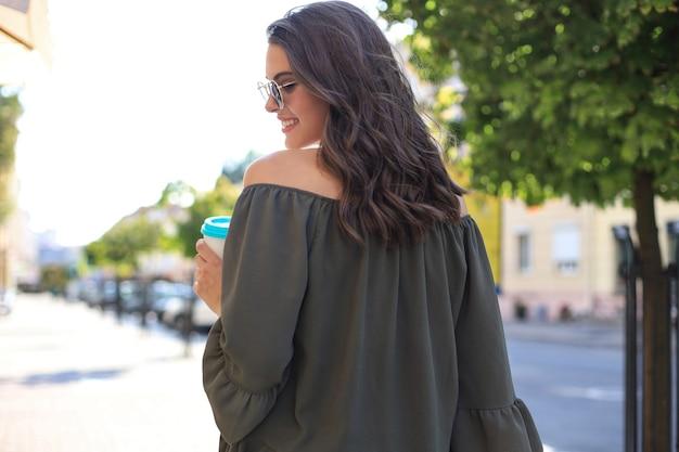 Zdjęcie uśmiechnięta ładna kobieta w zielonej sukience trzymając papierowy kubek, chodząc na zewnątrz ulicą.