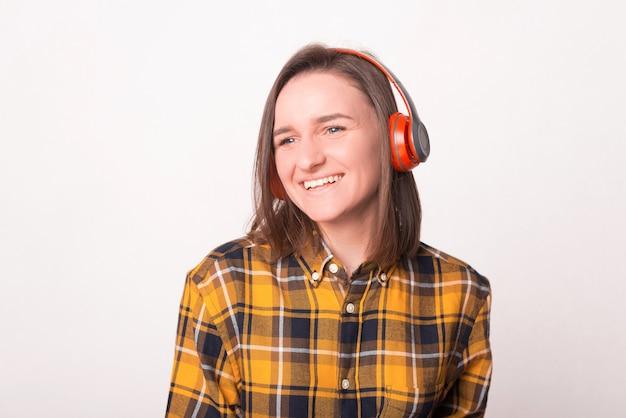 Zdjęcie uśmiechnięta młoda kobieta słuchania muzyki w słuchawkach i odwracając