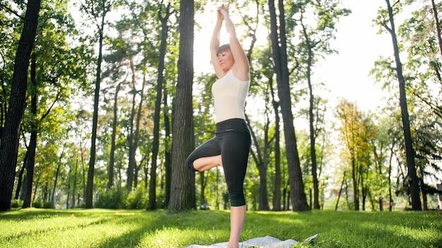 Zdjęcie uśmiechnięta szczęśliwa kobieta 40 lat robi ćwiczenia jogi na macie fitness w lesie. harmonia człowieka w naturze. osoby w średnim wieku dbające o zdrowie psychiczne i fizyczne