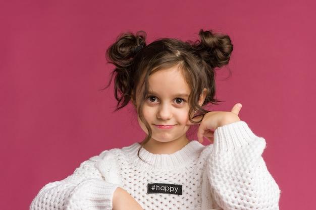 Zdjęcie uśmiechnięte dziecko dziewczynka na białym tle nad różowym