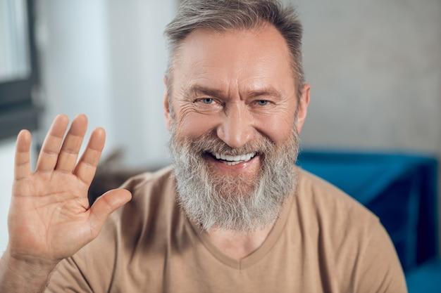 Zdjęcie uśmiechniętego brodatego mężczyzny od pasa w górę