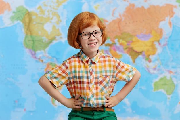 Zdjęcie uśmiechniętego chłopca z rudymi włosami, w okularach, trzymającego ręce w pasie, radującego się stojąc na tle mapy