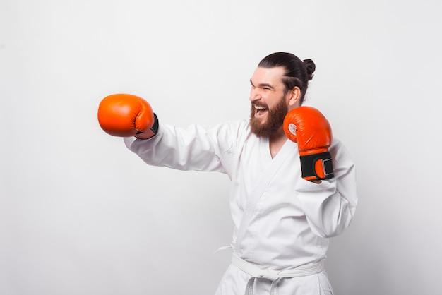Zdjęcie uśmiechniętego człowieka w mundurze taekwondo szkolenia na białej ścianie