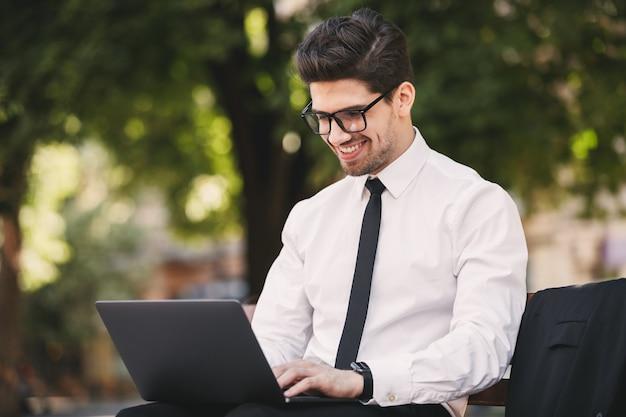 Zdjęcie uśmiechniętego mężczyzny w garniturze siedzącego na ławce w zielonym parku i pracy na laptopie w słoneczny dzień