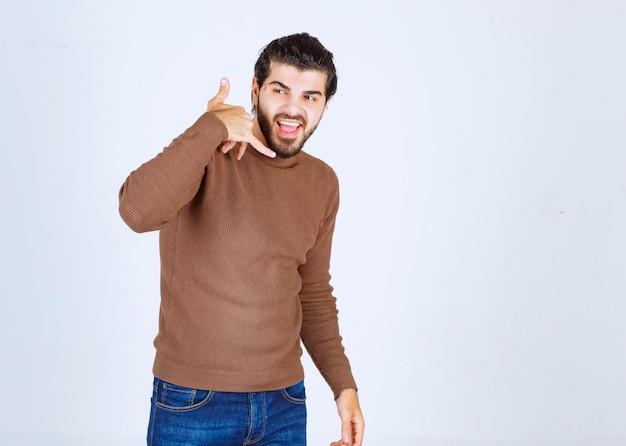 Zdjęcie uśmiechniętego młodego człowieka stojącego i pokazującego znak wywoławczy. zdjęcie wysokiej jakości