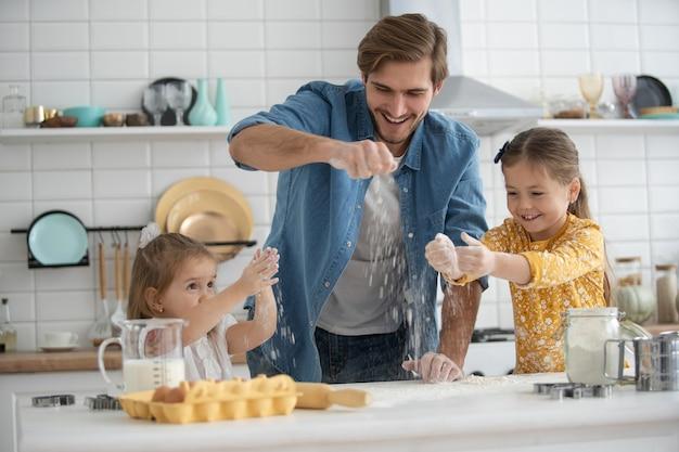Zdjęcie uśmiechniętego ojca i córek pieczenia w kuchni i zabawy.