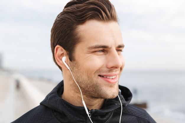 Zdjęcie uśmiechniętego sportowca w wieku 30 lat w czarnej odzieży sportowej, korzystającego ze słuchawek i telefonu komórkowego podczas spaceru promenadą nad morzem