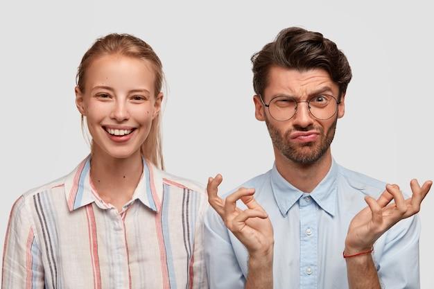 Zdjęcie uśmiechniętej jasnowłosej kobiety, wyraża radość, niezadowolony nieogolony mężczyzna o ponurym wyrazie, unosi brwi z niechęcią, rozkłada ręce, odizolowane na białej ścianie. emocje, reakcja
