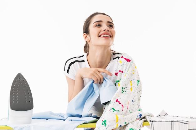 Zdjęcie uśmiechniętej kobiety gospodyni domowej w wieku 20 lat ubranej w odzież codzienną prasowanie czystych ubrań na desce odizolowanej nad białą ścianą