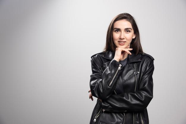 Zdjęcie uśmiechniętej kobiety stwarzającej w czarnej skórzanej kurtce