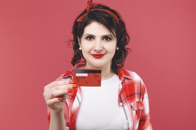 Zdjęcie uśmiechniętej ładnej dziewczyny trzymającej w dłoni czerwoną kartę kredytową