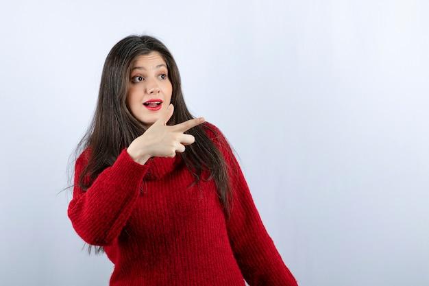 Zdjęcie uśmiechniętej młodej kobiety w czerwonym swetrze, wskazującej w bok