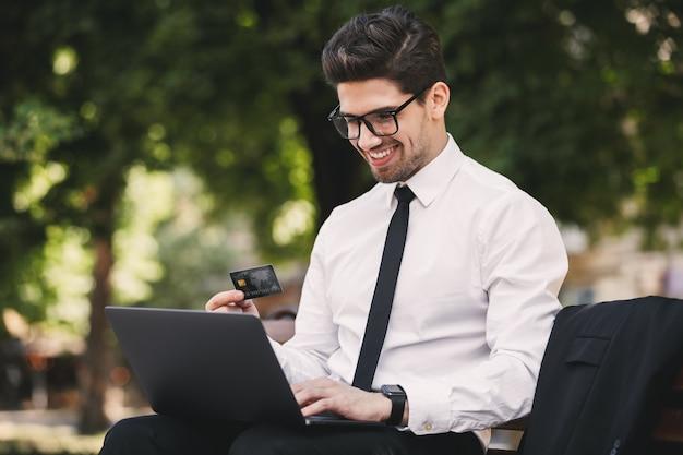 Zdjęcie uśmiechnięty biznesmen w garniturze siedzi na ławce w zielonym parku i pracuje na laptopie w słoneczny dzień