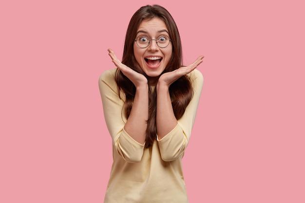 Zdjęcie uszczęśliwionej, radosnej kobiety, która trzyma ręce rozłożone w pobliżu twarzy, szczęśliwą i zaskoczoną dobrą nowiną, wyraża pozytywne emocje
