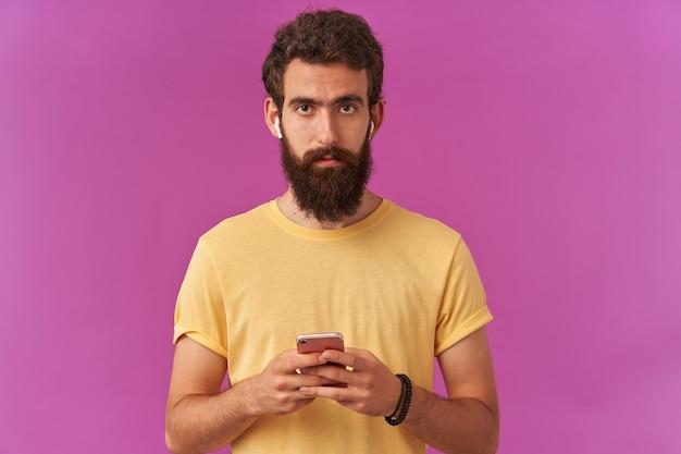 Zdjęcie uważnego, przystojnego brodatego młodego faceta trzyma telefon ze słuchawkami w dłoniach, skoncentrowanego stojącego nad fioletową ścianą