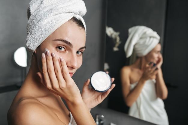 Zdjęcie uwodzicielskiej kobiety zawiniętej w ręcznik nakładający krem na twarz