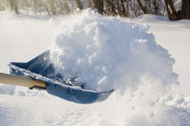 Zdjęcie w akcji. rzucanie śniegiem łopatą podczas czyszczenia podwórka