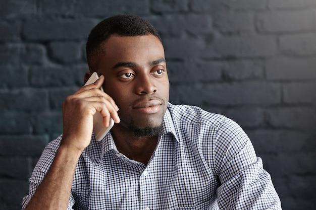Zdjęcie w głowę atrakcyjnego, młodego, ciemnoskórego mężczyzny w formalnym stroju o poważnym i pewnym siebie wyglądzie