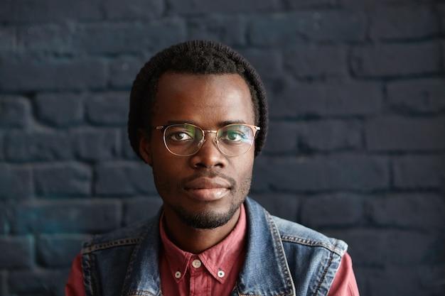 Zdjęcie w głowę atrakcyjnego młodego, nieogolonego ciemnoskórego mężczyzny w modnych ubraniach