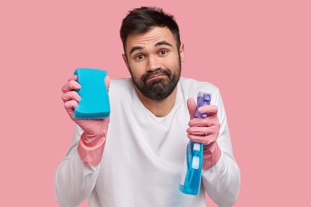 Zdjęcie w głowę brodatego młodego europejczyka z gęstą brodą, gumowych rękawiczek i białego swobodnego swetra, wygląda z niewyraźnym wyrazem twarzy