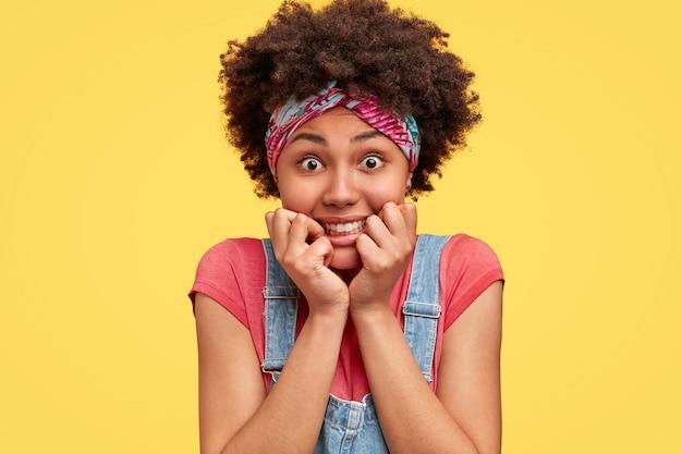 Zdjęcie w głowę kręconej samicy trzyma podbródek, ma pozytywny wyraz, otwiera oczy, przyjemny uśmiech, nosi opaskę i kombinezon, odizolowaną na żółtej ścianie. urocza młoda kobieta afroamerykanów.