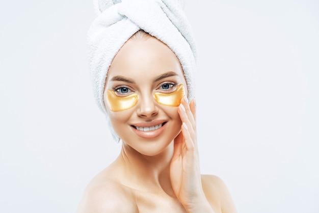Zdjęcie w głowę ładnej młodej europejki ma delikatny uśmiech, nosi złote łaty pod oczami, dba o twarz i skórę, nosi ręcznik kąpielowy na głowie, odizolowany na białej ścianie. koncepcja pielęgnacji skóry