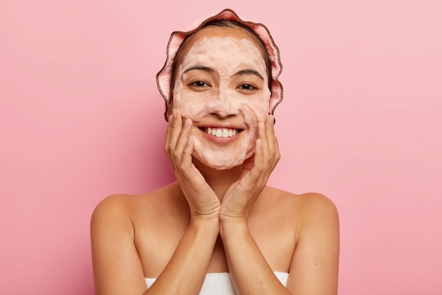 Zdjęcie w głowę młodej koreanki dotyka nieskazitelnie miękkiej skóry, myje twarz higienicznym mydłem z pieniącym środkiem myjącym, zawinięte w ręcznik, ma na głowie czepek kąpielowy, odizolowany na różowej ścianie. koncepcja czyszczenia