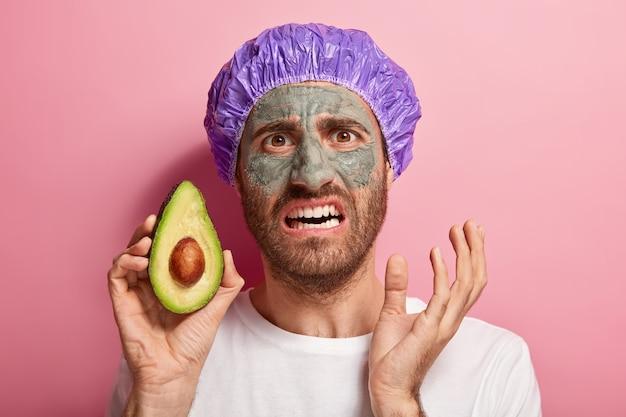 Zdjęcie w głowę niezadowolonego mężczyzny wykonującego swój rytuał kosmetyczny
