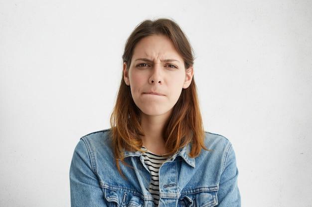 Zdjęcie w głowę niezdecydowanej, zdezorientowanej młodej europejki w dżinsowej sukience ścigającej usta, jej spojrzenie wyrażające wątpliwości i niepewność