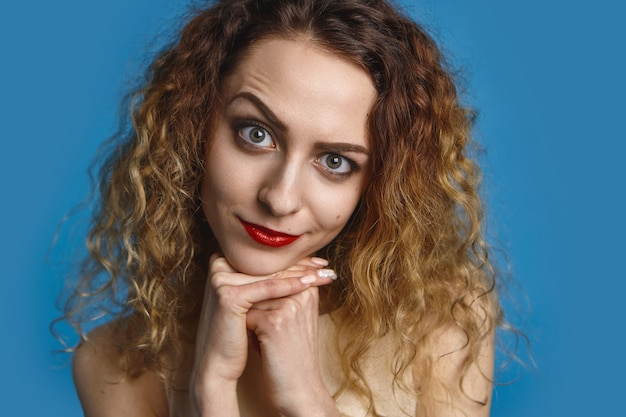 Zdjęcie w głowę pięknej eleagant dziewczyny z wolumoniuszowymi włosami i czerwonymi ustami o podejrzanym spojrzeniu, unoszącej brew i trzymającej ręce pod brodą. ładna kobieta patrząc z figlarnym wyrazem twarzy