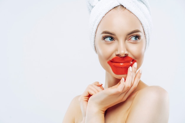 Zdjęcie w głowę pięknej młodej kobiety, która nosi hydrożelową maskę na spierzchnięte usta, ma zdrową gładką skórę, minimalny makijaż i manicure, wypróbowuje nowy kosmetyk. zabiegi kosmetyczne, koncepcja dobrego samopoczucia.