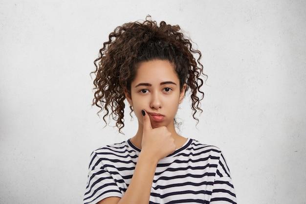 Zdjęcie w głowę pięknej ślicznej młodej kobiety o afro haitrstyle, trzymającej rękę na policzku, z zamyślonym i poważnym wyrazem twarzy