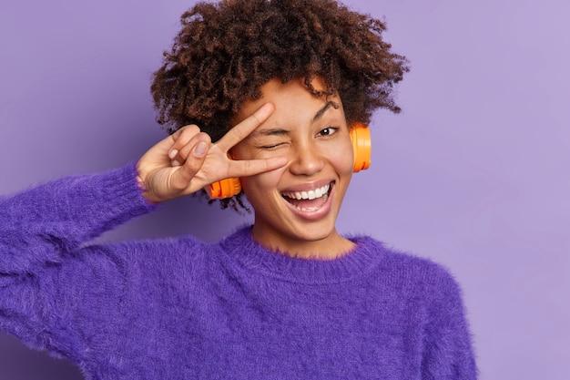 Zdjęcie w głowę pięknej, zabawnej ciemnoskórej kobiety mruga oczami i wykonuje gest pokoju, pokazując znak zwycięstwa, szeroko się uśmiecha, słucha muzyki przez słuchawki bezprzewodowe, nosi ciepły fioletowy sweter stoi w pomieszczeniu
