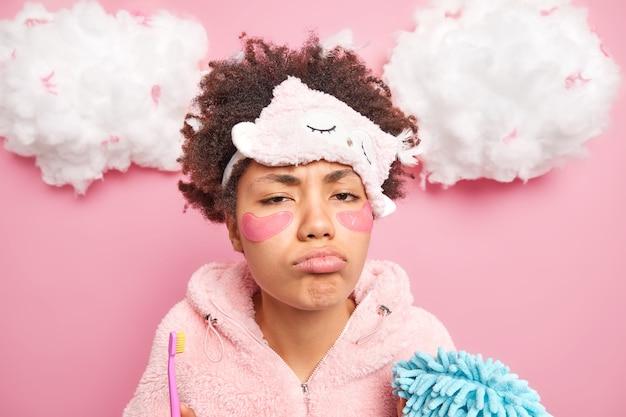 Zdjęcie w głowę posępnej, zrzędliwej etnicznej kobiety w torebkach usta wyglądają nieszczęśliwie z przodu, senność czuje się zmęczona codziennymi porannymi czynnościami, nosi maskę do spania i piżamę, nakłada kolagenowe łaty pod oczy