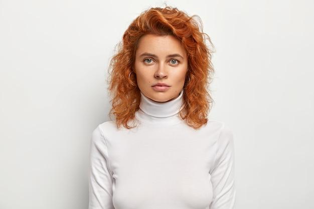 Zdjęcie w głowę poważnej, przystojnej kobiety wygląda poważnie, ma pewny wyraz twarzy, ma falowane rude włosy, nosi luźny golf, odizolowany na białej ścianie. koncepcja ludzi i piękna