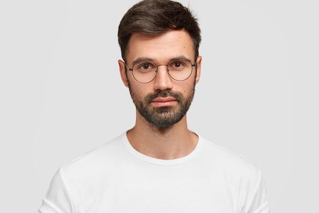 Zdjęcie w głowę przystojnego mężczyzny freelancera o atrakcyjnym wyglądzie, z ciemną brodą i wąsami, wygląda wprost poważnie, nosi białe codzienne ubrania. monochromia. wyrazy twarzy.